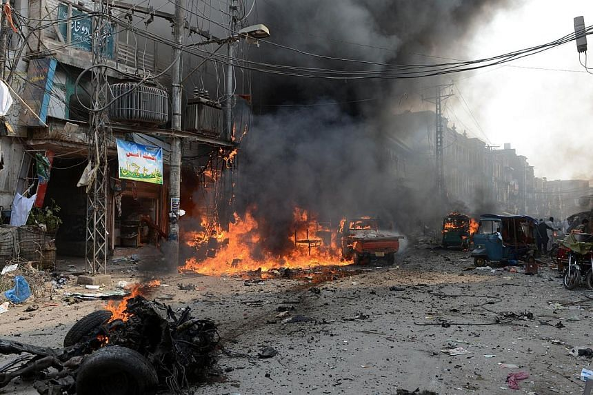 Vechiles and shops burn at the site of a bomb explosion in the busy Kissa Khwani market in Peshawar on Sunday, Sept 29, 2013. A bomb explosion killed at least 31 people in Pakistan's northwestern city of Peshawar on Sunday, Sept 29, 2013, officials s