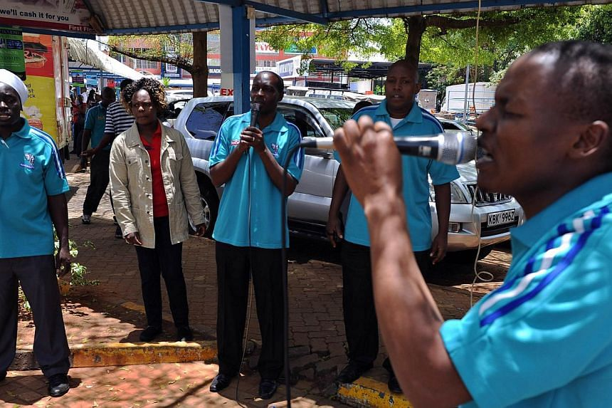 Staff members of Nakumatt supermarkets, who survived the four-day siege by Somali jihadists earlier in the week, pray on Sept 29, 2013 for the victims outside the Westgate mall. The death toll from the, Sept 21, 2013, attack by Islamist militants aga