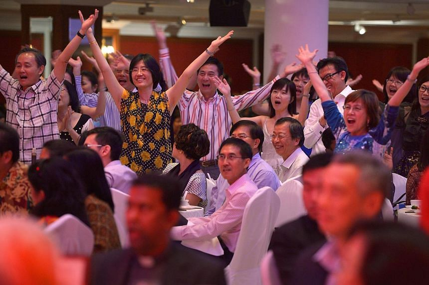 Diners singing along to the song Y.M.C.A, which was one of several popular 1970s hits, sung by a group from the Church of St Vincent de Paul in celebration of its 50th anniversary. The dinner was held at Orchid Country Club yesterday. -- ST PHOTO: KU