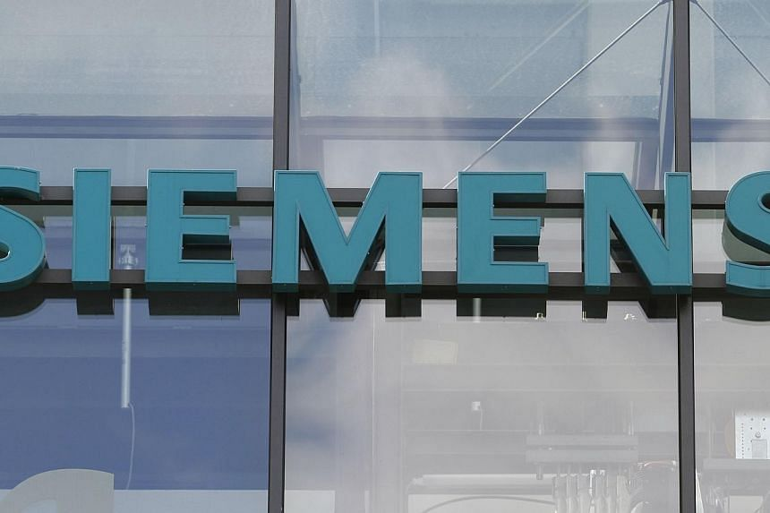 The logo of the German industrial giant Siemens AG at the historic construction plant in Berlin on Oct 12, 2011. German engineering giant Siemens said on Sunday that it plans to slash 15,000 positions worldwide by late next year as part of a cost-cut