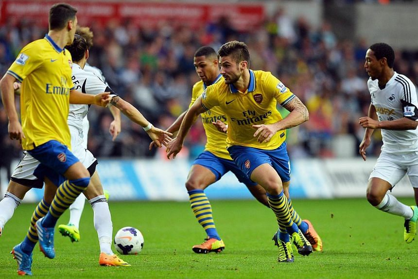 Arsenal's French striker Olivier Giroud (right) breaks clear during the English Premier League football match between Swansea City and Arsenal at The Liberty Stadium in Swansea, south Wales on September 28, 2013. -- PHOTO: AFP