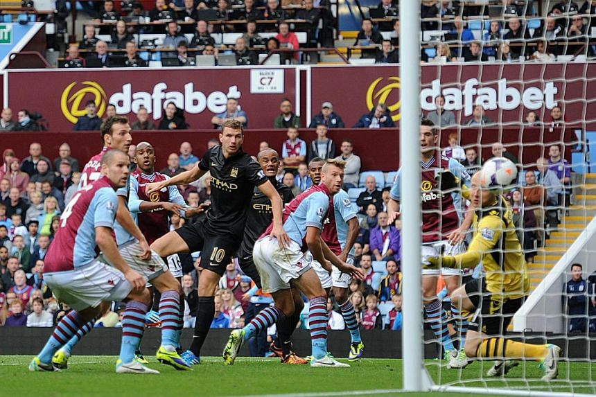 Manchester City's Edin Dzeko (centre left) scores his side's second goal of the game during their English Premier League match against Aston Villa, at Villa Park, in Birmingham, England, Saturday, Sept 28, 2013. Manchester City were brought down to e