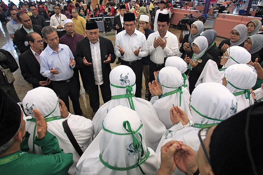 Minister in-charge of Muslim Affairs Dr Yaacob Ibrahim joins pilgrims to the Haj in prayer at Changi Airport Terminal 2 on Sept 22, 2013. Dr Ibrahim announced on Sunday morning that Singapore has received another 136 places for the haj. -- ST FILE PH