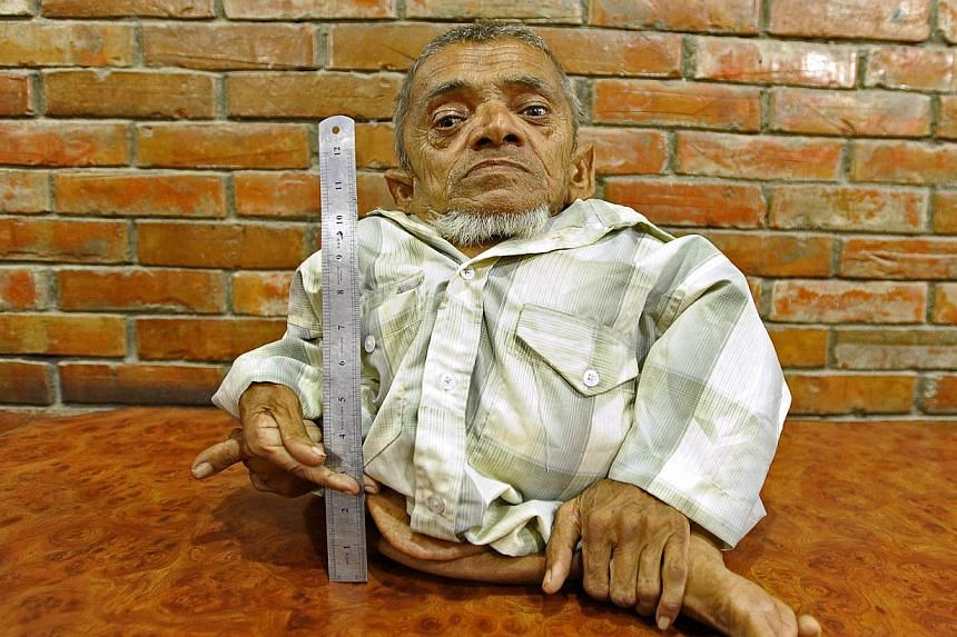Master Nau, a 73-year-old Nepali, who claims to be the world's shortest man in the Guinness World Records' immovable category, poses for a photo next to a ruler in Kathmandu on Sept 17, 2013.An elderly Nepalese man who is just 41cm tall is step
