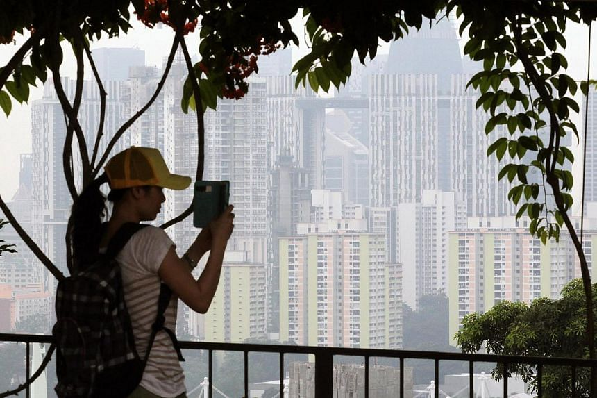 A woman taking photographs of the scenary from Mount Faber as she is silhouetted against the hazy background on Aug 20, 2013. The Pollutant Standards Index (PSI) on Monday afternoon climbed to a three-hour average of 47 at 2pm as people around S