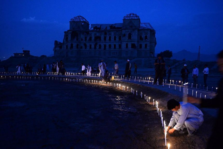 Afghan youth light candles in front of the destroyed palace of Darul Aman to mark the killing of 5000 civilians by the communist regime during the Russian occupation, in Kabul on Sept 29, 2013. Afghanistan began two days of official mourning for peop