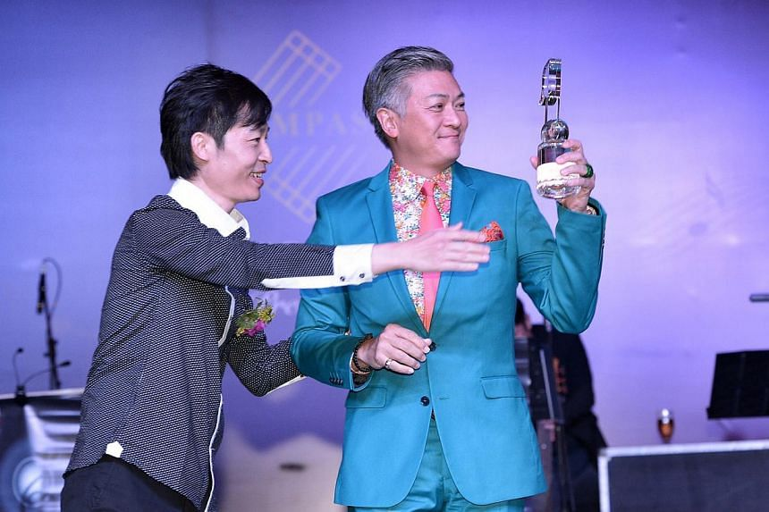 Composer Dick Lee (right) receiving the award for top local English pop song from Compass director Liang Wern Fook last night.