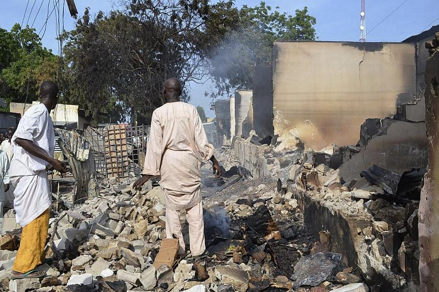 Residents watch as two men walk amidst rubble after Boko Haram militants raided the town of Benisheik, west of Borno State capital Maiduguri on Sept 19, 2013. Boko Haram gunmen on Sunday opened fire in a college dormitory in north-east Nigeria as the