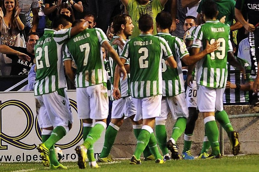 Betis' football players celebrate after scoring their first goal during the Spanish league football match Real Betis vs Villarreal CF at the Benito Villamarin stadium in Sevilla on Sept 29, 2013. Villarreal suffered their first defeat since returning