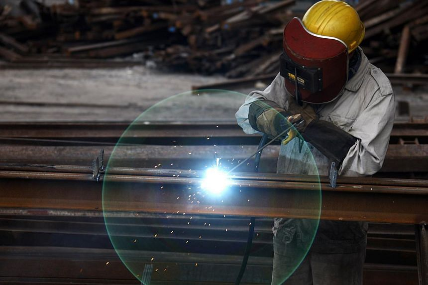 A worker welds at a machinery manufacturing factory in Huaibei, Anhui province Aug 20, 2013. China's manufacturing activity expanded for a second straight month in September, HSBC reported on Monday, suggesting a rebound in the world's second-biggest