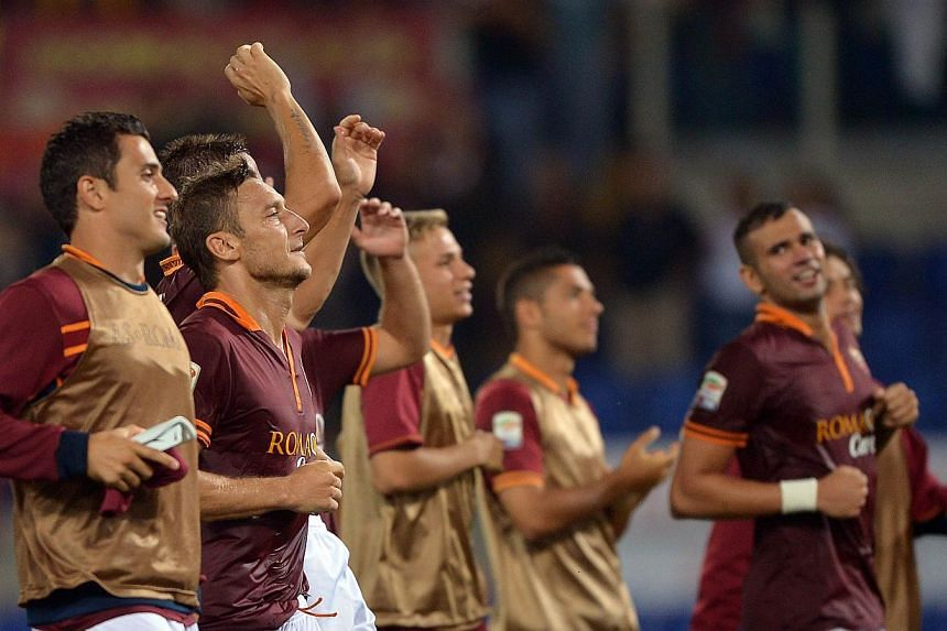 AS Roma's forward Francesco Totti (second left) celebrates with teammates at the end of the Serie A football match AS Roma vs Bologna at the Olympic Stadium on Sept 29, 2013, in Rome. AS Roma's superb start to the season continued with a 5-0 rout of