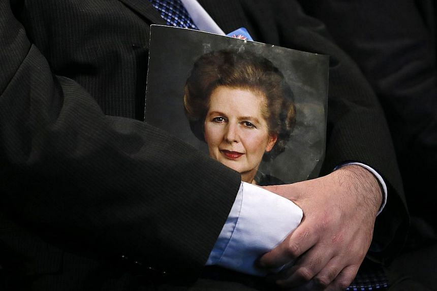 A delegate holds a portrait of Margaret Thatcher during a tribute to the former conservative prime minister on the opening day of The Conservative Party annual conference in Manchester, northern England on Sept 29, 2013. Britain's Conservatives paid