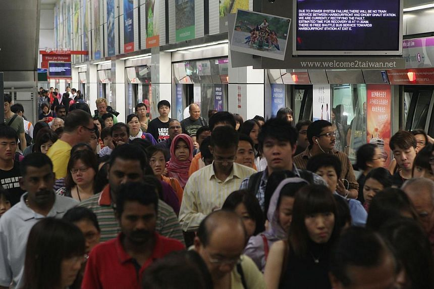 Commuters at Dhoby Ghaut MRT station during the disruption of train service on March 15, 2012. SMRT and SBS Transit have been fined a total of $1.1 million for a series of train delays and safety lapses in the last 10 months. -- ST FILE PHOTO:&n