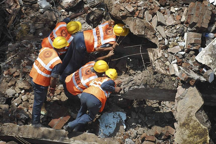 Rescue crews search for survivors at the site of a collapsed residential building in Mumbai on Sept 28, 2013.Indian police on Tuesday, Oct 1, 2013, arrested three officials working for the Mumbai city government over the collapse of an apartmen