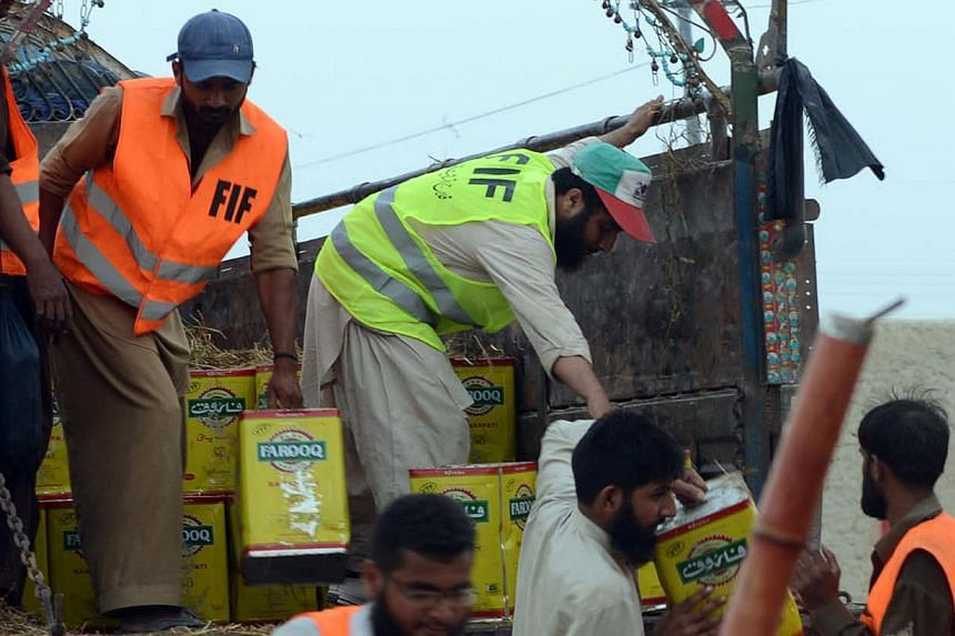 Pakistani volunteers unload relief supplies for earthquake victims in the earthquake-devastated district of Awaran on Monday, Sept 30, 2013. The death toll from a strong quake that hit south-west Pakistan last week rose to 376 on Tuesday, Oct 1,