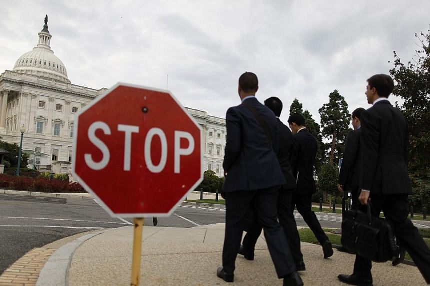 Visitors walk past a stop sign on the Senate side of the US Capitol in Washington on Oct 1, 2013.As expected, the United States Senate on Tuesday voted to kill Republicans' latest attempts to modify an emergency government funding Bill, just ho