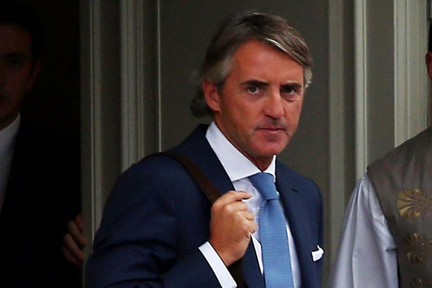 Italian football coach Roberto Mancini walks out of a hotel after holding talks with Galatasaray in Istanbul on Sept 30, 2013. Galatasaray on Monday finalised the appointment of Roberto Mancini as their new coach on a three-year deal to replace the s