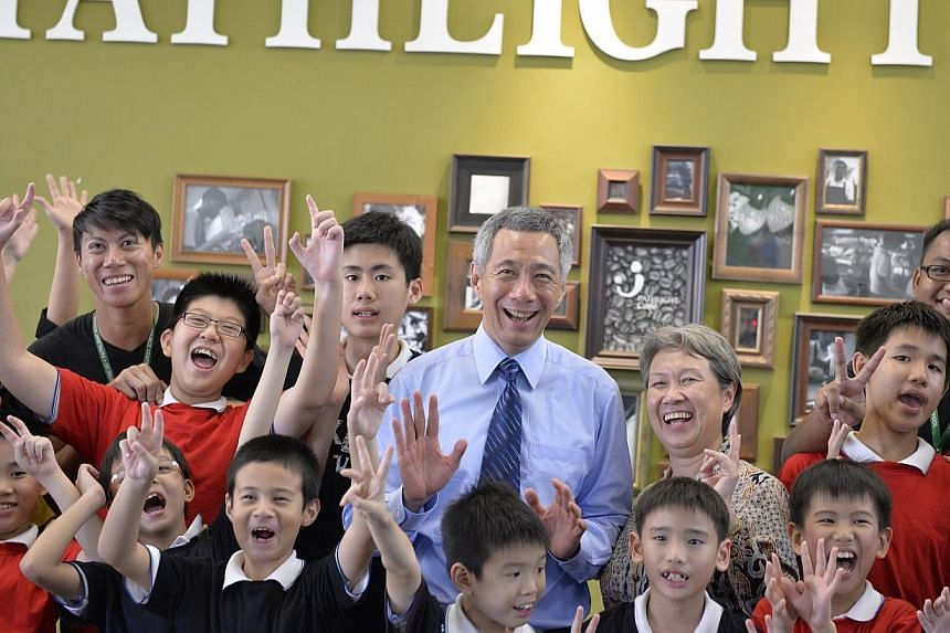 Prime Minister Lee Hsien Loong (centre) and his wife Ho Ching (back row, third from right) pose for pictures with students from special needs school Pathlight.The Government will do more for special education students as part of its drive to bu