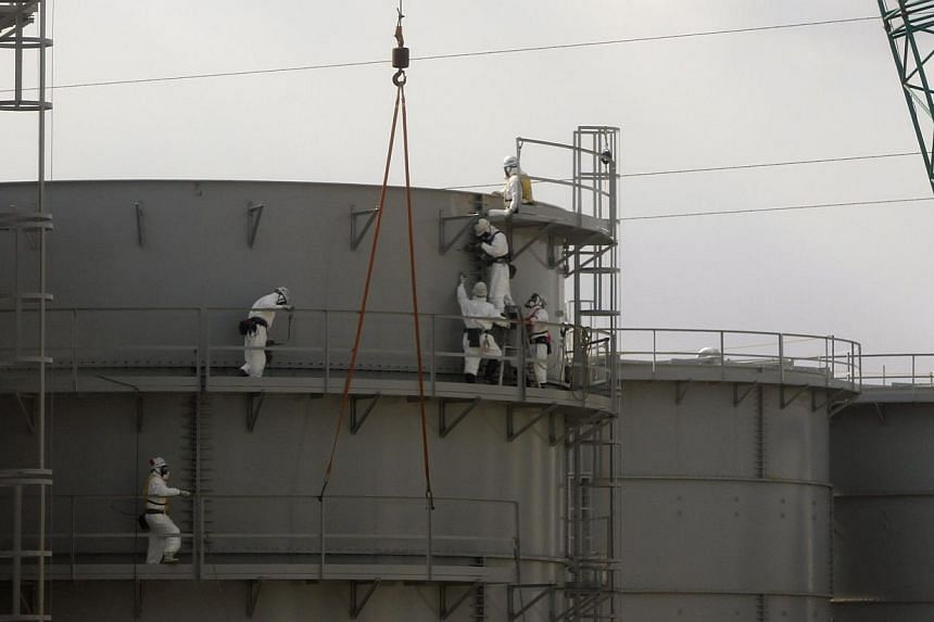 Workers wearing protective suits and masks constructing water tanks are seen through a bus window at Tokyo Electric Power Co. The operator of the crippled Fukushima nuclear plant said on Tuesday that four tonnes of rainwater that may be contaminated