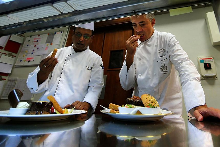 French chef Sandro Gamba (right) tastes a camel burger dish alongside another chef at a luxurious hotel in Abu Dhabion Sept 16, 2013.-- FILE PHOTO: AFP
