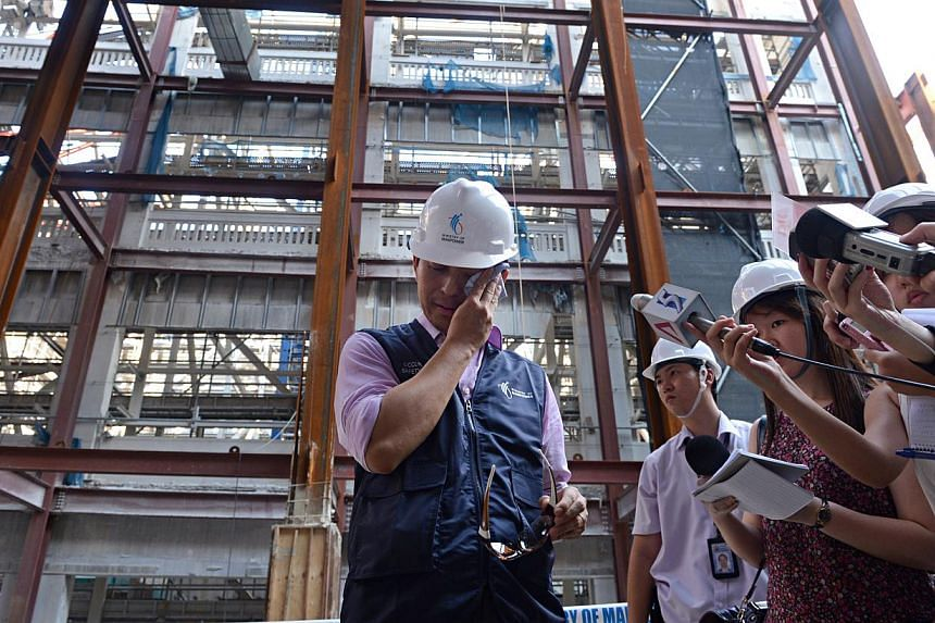 Acting Manpower Minister Tan Chuan-Jin (left) wiping off sweat while visiting the construction site where the crane accident happened yesterday. He says the next step is to determine what exactly happened so that lessons can be learnt and rectificati