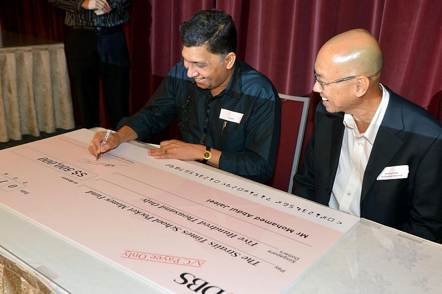 Businessman Mohamed Abdul Jaleel signing a cheque for $500,000 to The Straits Times School Pocket Money Fund yesterday, with fund chairman Han Fook Kwang beside him. This is his third donation to the fund. -- ST PHOTO: KUA CHEE SIONG