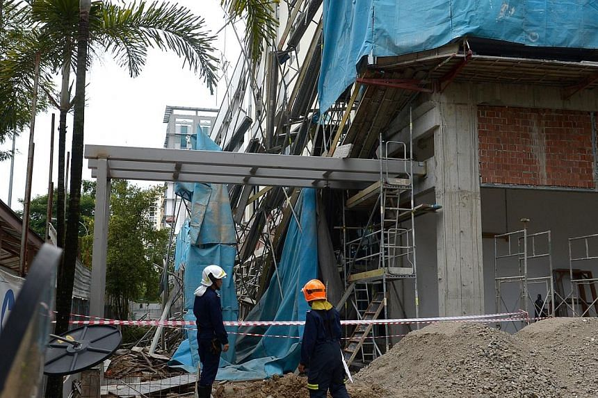SCDF officers inspecting the scene at the construction site along Braddell Road. -- ST PHOTO: JAMIE KOH