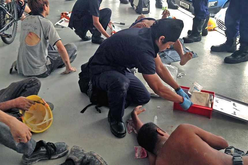 Injured workers receive treatment after a worksite accident at a construction site along Braddell Road. -- PHOTO: SHIN MIN