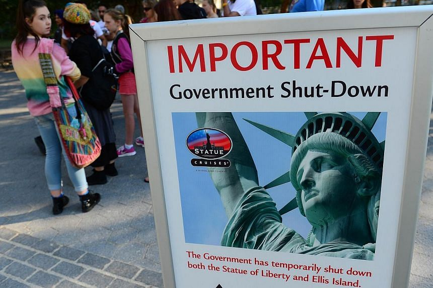 Tourists walk by a sign announcing that the Statue of Liberty is closed due to a US government shutdown in New York, Oct 1, 2013. -- PHOTO: AFP