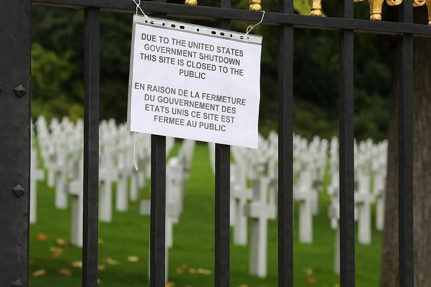 A notice advising visitors that the American Cemetery is closed due to the partial shutdown of the US federal government hangs from the gates of the cemetery in Suresnes, west of Paris, Tuesday Oct 1, 2013. -- PHOTO: AFP