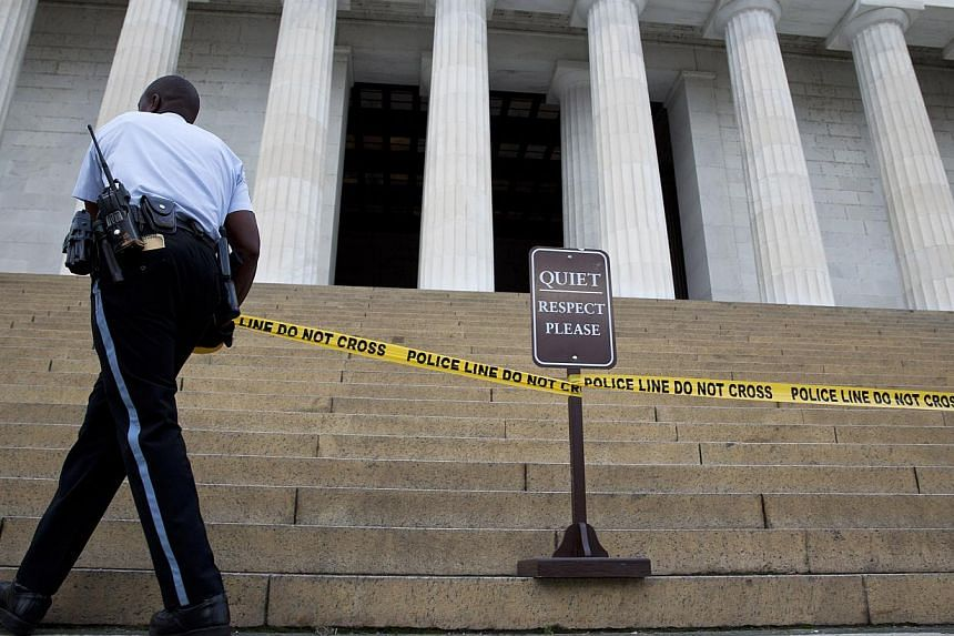 A member of the Park Police places police tape in front of the Lincoln Memorial due to a partial government shut down in Washington, DC, US on Tuesday, Oct 1, 2013. -- PHOTO: AFP