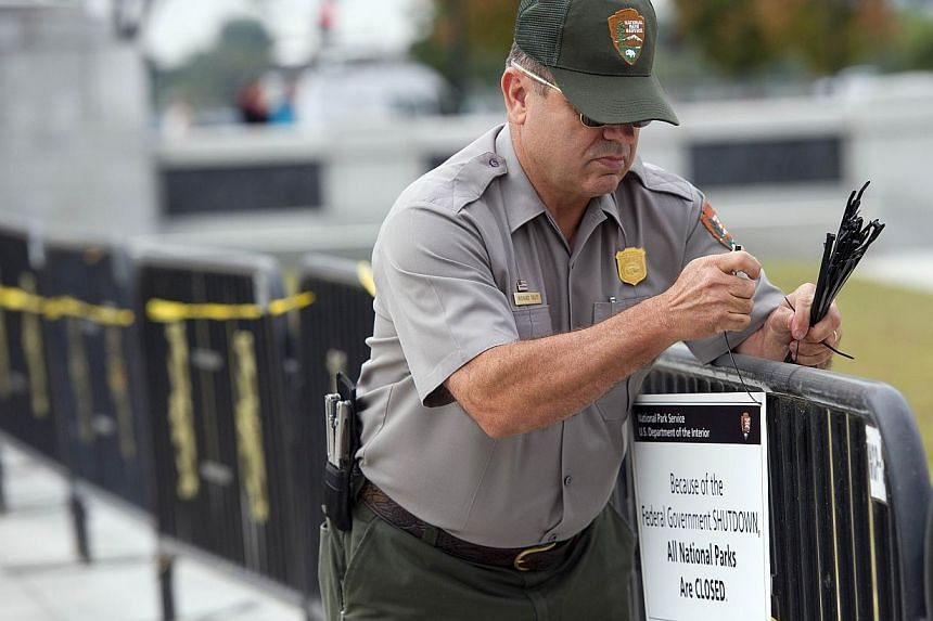 US Park Ranger Richard Trott places a closed sign on a barricade in front of the World War II monument in Washington, DC, Oct 1, 2013. -- PHOTO: AFP