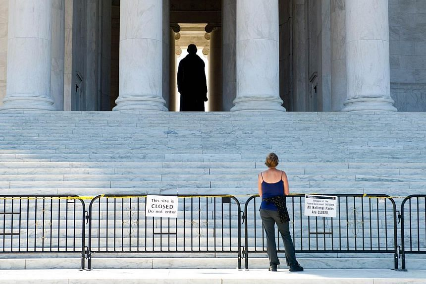 A woman views the Jefferson Memorial from behind barricades in Washington, DC, on Oct 1, 2013. -- PHOTO: AFP