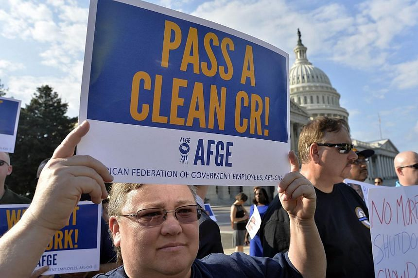 Protesters display placards during a demonstration in front of the US Capitol in Washington on Oct 1, 2013 urging Congress to pass the budget bill. -- PHOTO: AFP