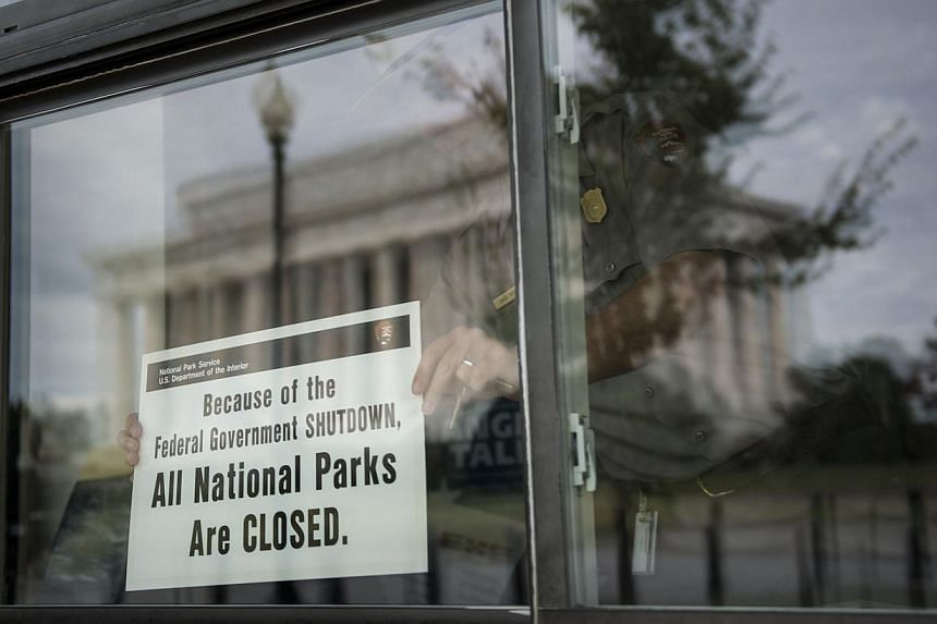 A US Park Ranger places a closed sign inside an information booth at the Lincoln Memorial on the National Mall, Oct 1, 2013 in Washington, DC. -- PHOTO: AFP