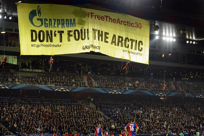 Greenpeace activists display a banner, during the Champions League group E group stage soccer match between Switzerland's FC Basel and Germany's FC Schalke 04 at the St. Jakob-Park stadium in Basel, Switzerland, Tuesday, Oct 1, 2013. Greenpeace campa