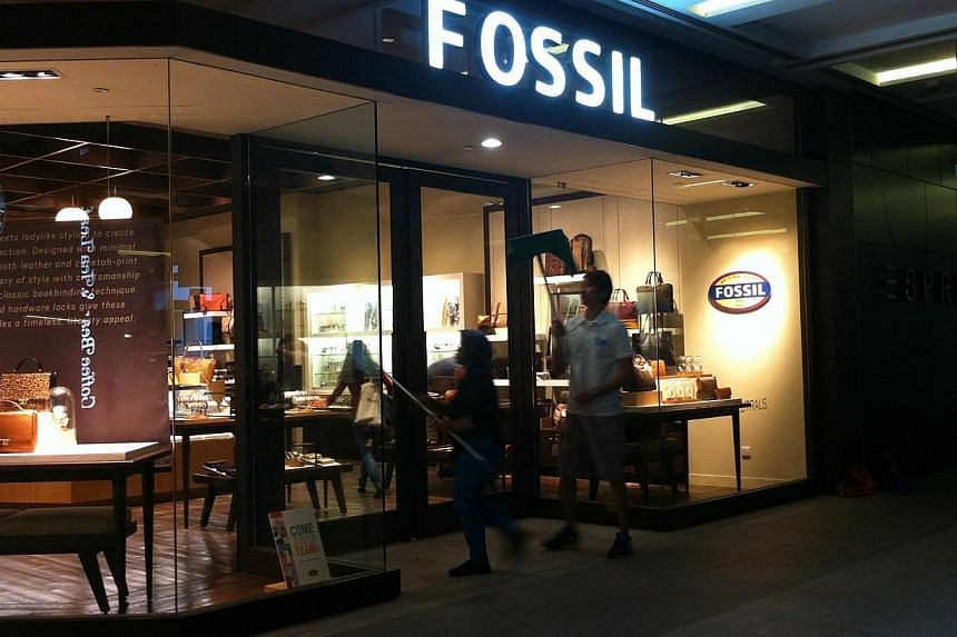 Staff at Fossil on the first floor of the Jem mall cleaning up before opening time.-- ST PHOTO: JESSICA LIM