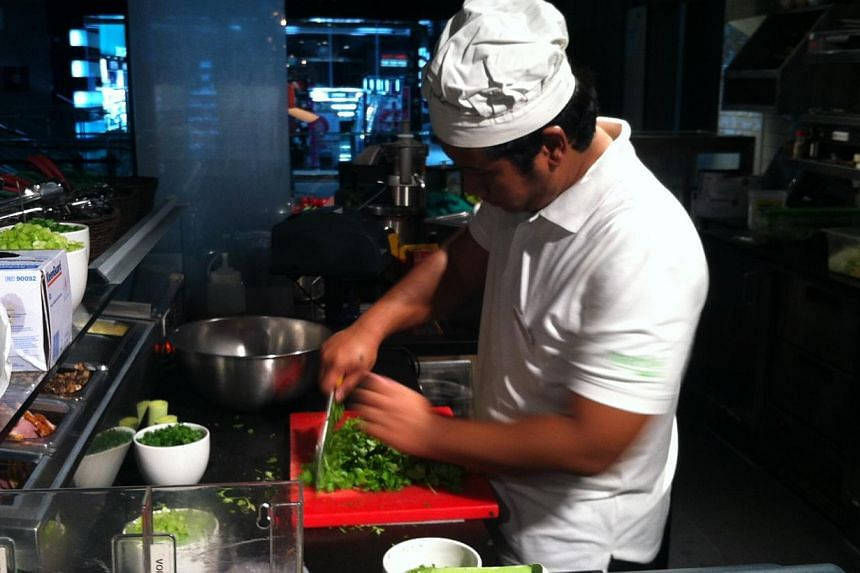 A kitchen hand at the Marche outlet in Jem chops parsley as part of the food prep for the day ahead of Jem's reopening on Wednesday.-- ST PHOTO: JESSICA LIM