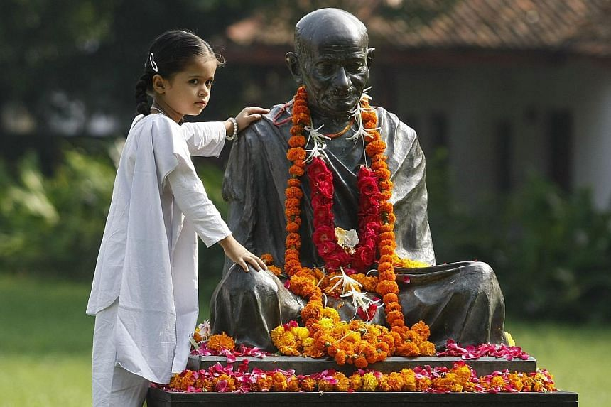 """A schoolgirl posing for a picture next to a statue of Mahatma Gandhi during celebrations to mark the 144th birth anniversary of Gandhi, at Ahmedabad in the western Indian state of Gujarat on October 2, 2013. Mahatma Gandhi, also known as the """"Father"""