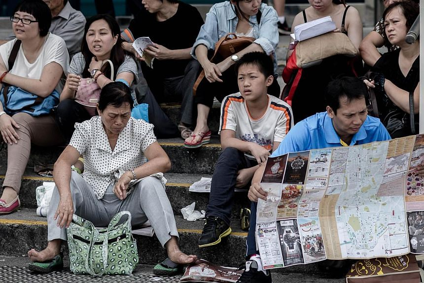 Chinese tourists visiting a popular waterfront promenade in Hong Kong on October 2, 1013. China's National Tourism Administration publicised a 64-page Guidebook for Civilised Tourism -- with illustrations to accompany its list of dos and don'ts -- on