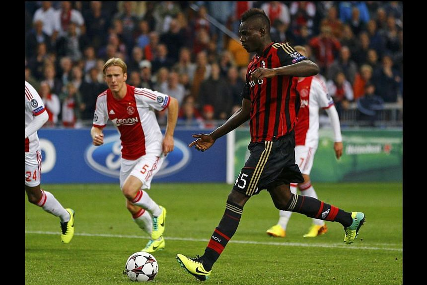 AC Milan's Mario Balotelli scores on penalty against Ajax Amsterdam during their Champions League soccer match at the Amsterdam Arena stadium Oct 1, 2013. Mario Balotelli scored a penalty in the fourth minute of added time to earn AC Milan a 1-1 draw