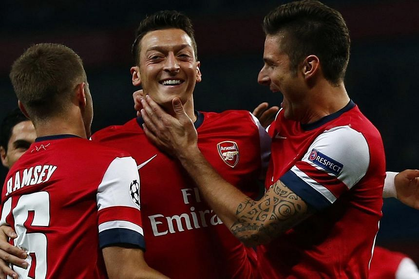 Arsenal's Mesut Oezil (centre) celebrates with teammate Olivier Giroud (right) after scoring a goal against Napoli during their Champions League soccer match at the Emirates stadium in London on Oct 1, 2013. Oezil bewitched Napoli to conjure up a 2-0