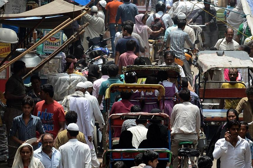 Indian commuters travel through a market area of New Delhi on July 10, 2013. -- FILE PHOTO: AFP