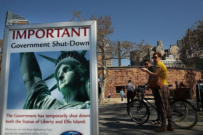 People look at a sign informing them that the Statue of Liberty is closed due to the government shutdown in Battery Park on Oct 1, 2013 in New York City. Where once she welcomed immigrants pursuing the American dream and more recently hordes of touri