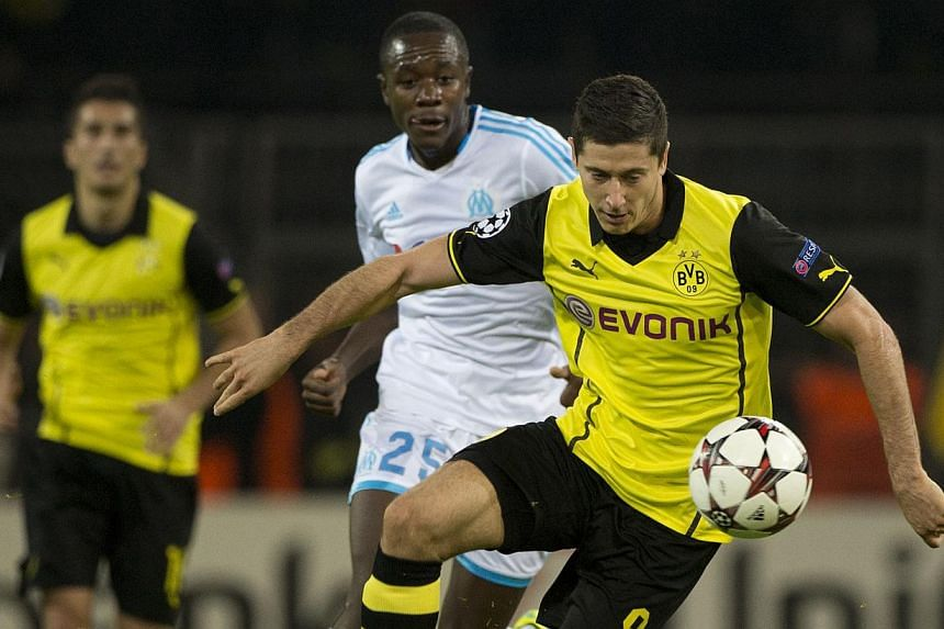 Dortmund's Polish striker Robert Lewandowski runs with the ball during the UEFA Champions League Group F football match Borussia Dortmund vs Olympique Marseille in Dortmund, western Germany on Oct 1, 2013. Dortmund won the match 3-0. Last season's be