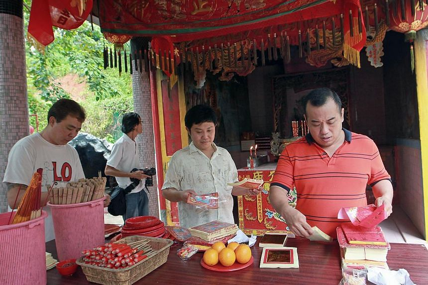 Members of the public with their offerings seen at the Tua Pek Kong Main Temple, the oldest temple on Pulau Ubin on Oct 2, 2013. -- ST PHOTO: NEO XIAOBIN