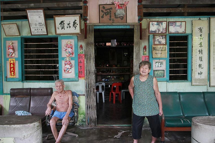 The oldest son of the village head Mr Lin Chu Zi (left), 82, and his wife Madam Chen Siew Zhen (right), 75, at 427 Pulau Ubin, still resides in his father's residence with their son. -- ST PHOTO: NEO XIAOBIN