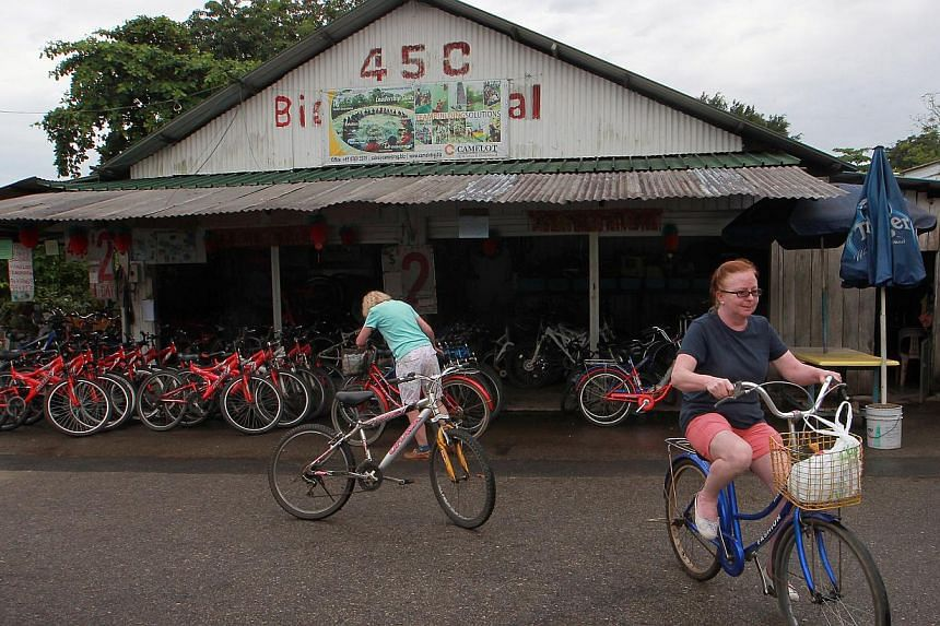 Tourists seen at a bicycle rental shop located at the village centre, described by a resident as the Orchard Road of Pulau Ubin. -- ST PHOTO: NEO XIAOBIN