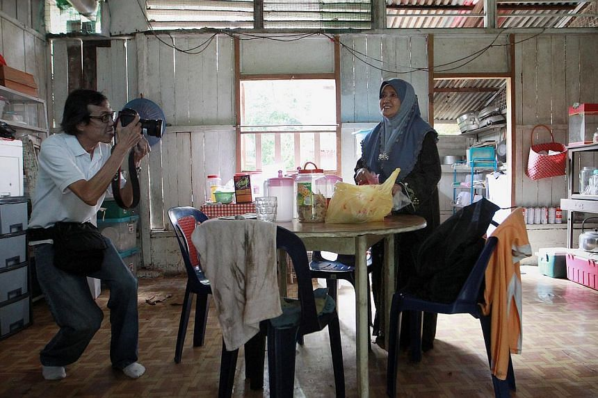 A media photographer shoots Kampong Durian/Kampong Melayu resident Madam Hajah Maimunah Bte Abdullah (right), 87, in the kitchen area which they use to conduct cooking classes, on Oct 2, 2013. -- ST PHOTO: NEO XIAOBIN