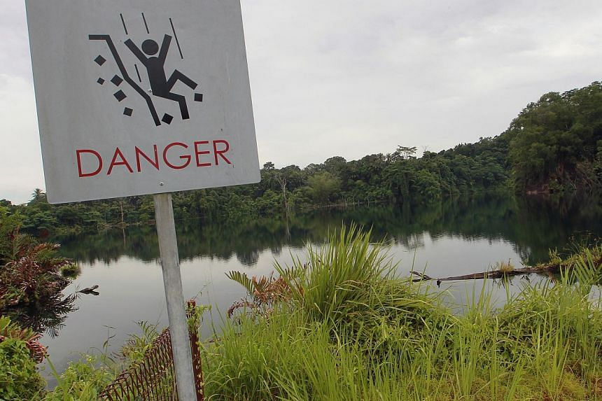 A warning sign situated at the Pekan Quarry, also known as the Ho Man Choo Quarry in Pulau Ubin on Oct 2, 2013. -- ST PHOTO: NEO XIAOBIN